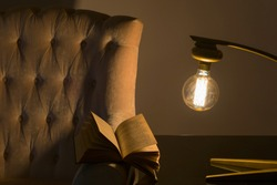 Open book on old cozy armchair with golden torch lamp on the table
