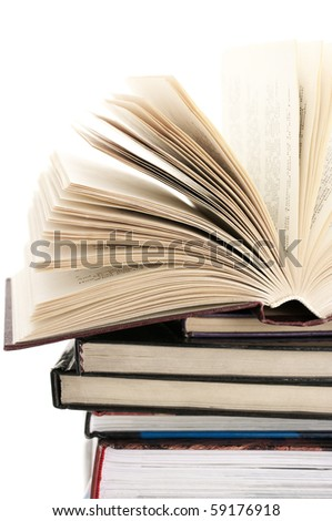 Open book on stack of various books against white background.