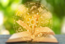 Open book on table and illustration of zodiac wheel with astrological signs against blurred green background