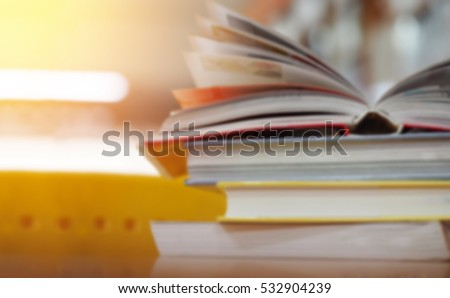 Open book on wood desk in the library room with blurred focus for background, education back to school concept