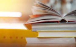 Open book on wood desk in the library room with blurred focus for education background and back to school concept