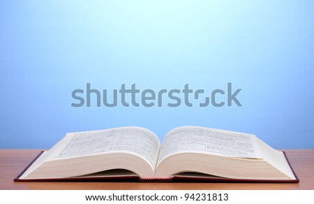 Open book on wooden table on blue background