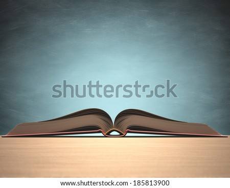 Open book over the table with blackboard on background Clipping path included