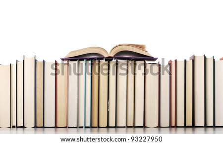 Open book resting on stack of books.white background
