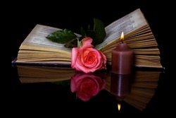 Open book, Rose and a burning candle on a black background