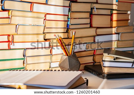 Open book, textbook, laptop, pencils in library, stack piles of literature text archive, bookshelves in school study class room background for academic education learning concept #1260201460