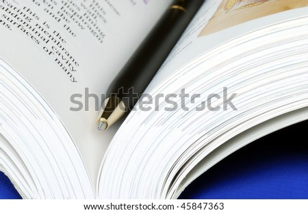 Open book with a pen isolated on blue