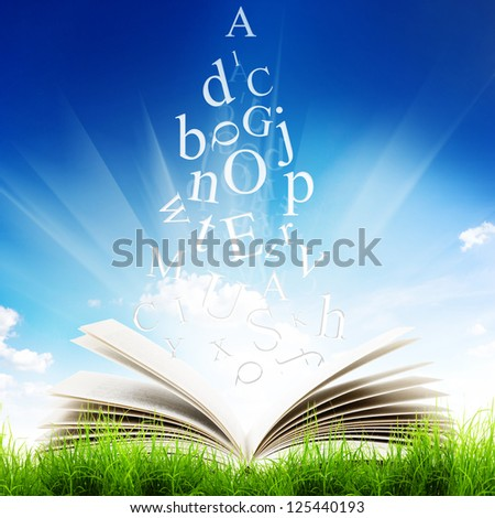 Open book with flying letters in green grass over blue sky background. Magic book - stock photo