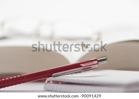 Open book with glasses and a pen to take notes