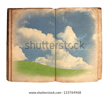 Open book with green meadow and clouds on white background - stock photo