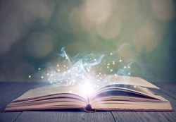 Open book with magic glowing on wooden table. Fairy tale