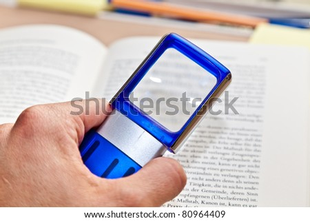 Open book with magnifying glass
