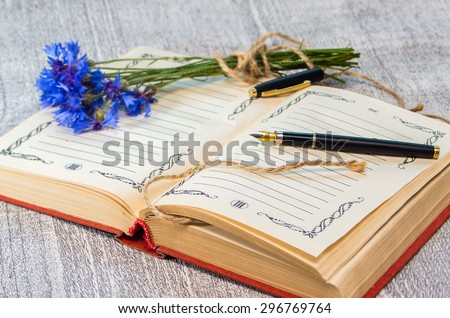 open book with pen and blue cornflowers in the background. Intentional blur.