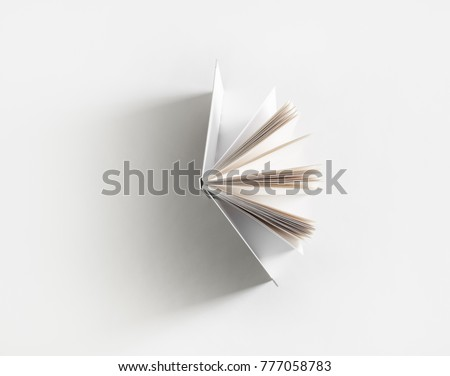 Open book with soft shadow on white paper background. #777058783