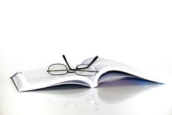 Open book with spectacles or reading glasses resting on it, isolated on a white background.