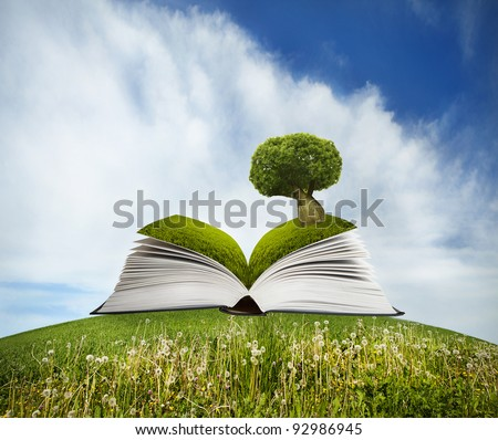 Open book with tree on grass field and blue sky