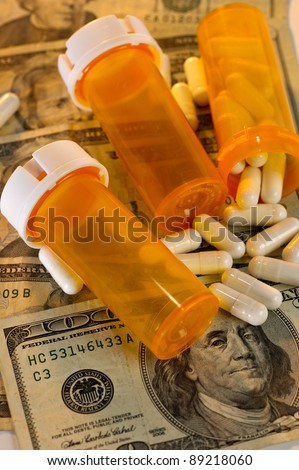 Open bottle of pills spilling out on top of US currency, along with empty bottles. Showing how much less one gets for the money when it comes to the rising cost of health care.