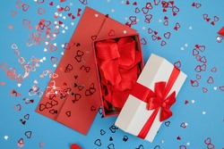 Open box filled with rose leaves with red envelope on blue background. Present with love postcard with glitter hearts around. Gift from love on valentines day