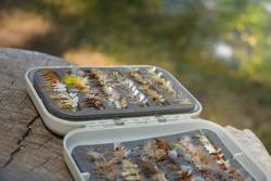 Open box of fly fishing mayfly and caddis dry flies outdoors on a stump.