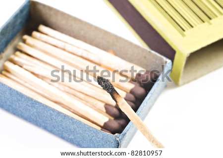 Open box of matches with one match burning