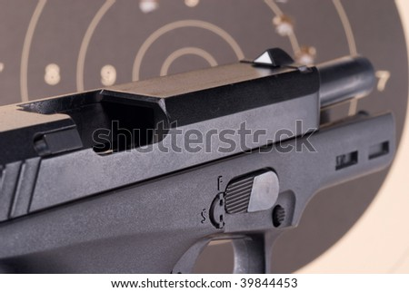 Open breech of a large 9mm pistol with target behind