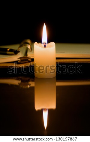 Open burning candle diary and pen