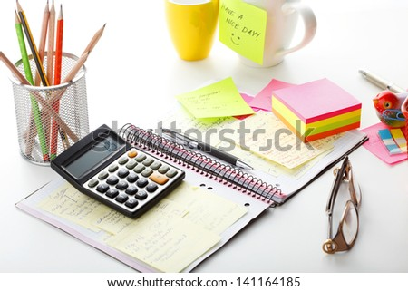 """Open business diary with pink and yellow """"Post It"""" notes, calculator and with office supplies. Shallow focus."""