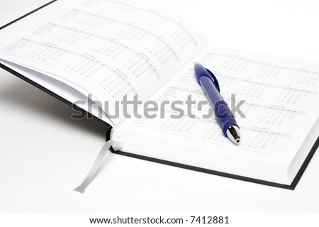 open calendar with blue pen isolated on white