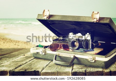 open case with old camera sunglasses and clock in front of seascape. filtered image.