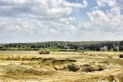 Open cast mine pit. One truck,full, goes up and another,empty, goes down.