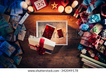 Open Christmas gift box with a tablet and a smart phone inside, presents and letters all around, top view