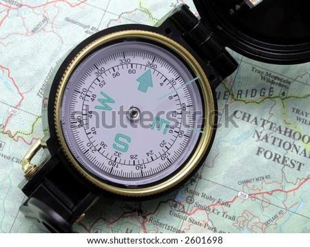 Open compass pointing North on topographical map
