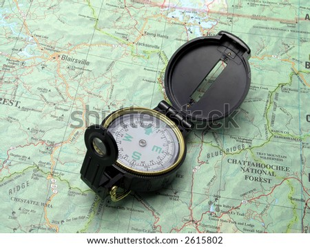 Open compass pointing North on topographical map - stock photo