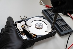 open Computer Hard Drive on white background screwdriver in  Hands in black gloves. master of repair.