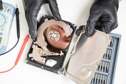 open Computer Hard Drive on white background with screwdriver set. Hands in black gloves. master of repair.
