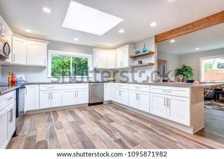 Open concept kitchen with skylight, white cabinets and hardwood floor.