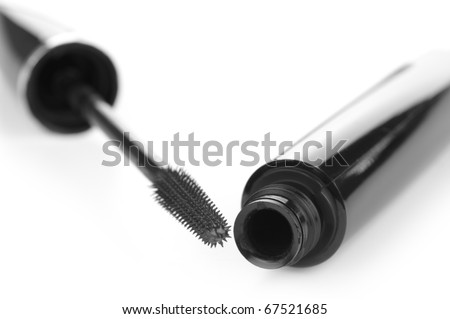 Open container of mascara and brush on white background. Shallow DOF.