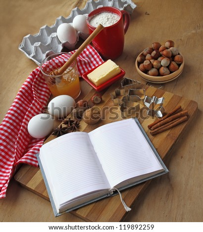 Open culinary book with a towel, butter, cup of flour, egg and pie-pans