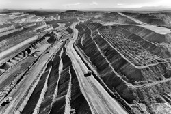 Open cut coal mine in Hunter valley region supplying Liddell and Baywaters power stations excavating coal by huge trucks from the botton via serpentine road.