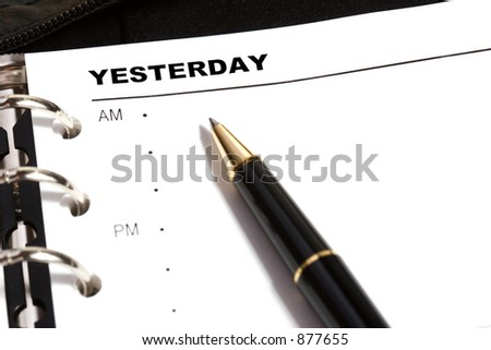 Open dayplanner with a ballpoint pen pointing to YESTERDAY.