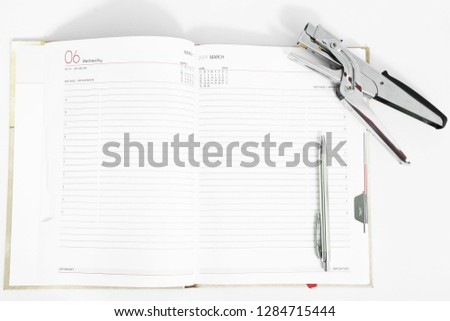 Open diary with pen and stapler. Isolated on the white background.