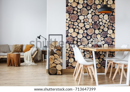 Open dining room interior with firewood, communal table and wooden log wall decoration for warm cozy atmosphere