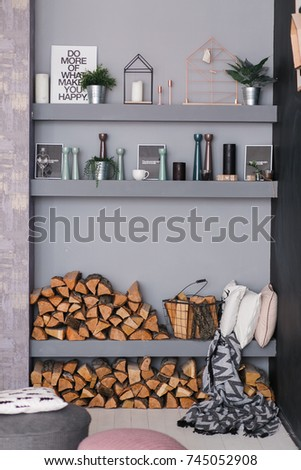 Open dining room interior with firewood, shelves on the grey wall and wooden log wall decoration for warm cozy atmosphere #745052908