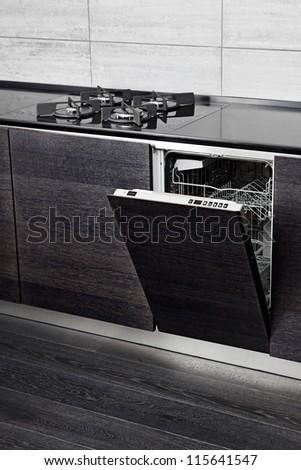Open dish washer machine and gas-stove on black hardwood kitchen