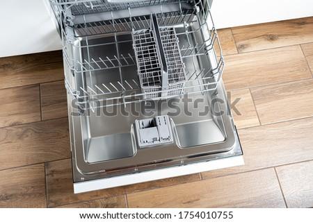 Open dishwasher. Trays of dishwasher