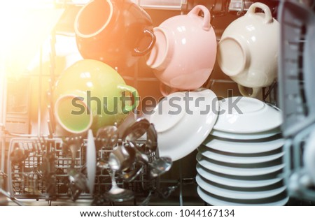 Open dishwasher with clean glass and dishes, selective focus, Clean after washing in the dishwasher. bright colorful dishes