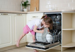 Open dishwasher with dirty dishes. Little girl helps to lay the dishes. Mom's little helper. Kitchen