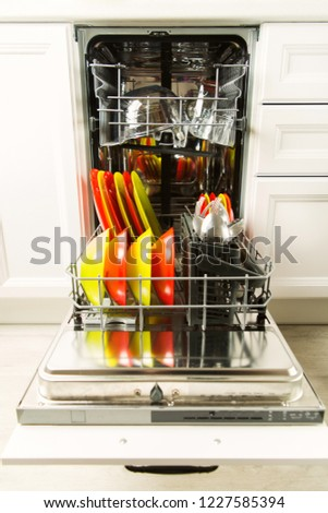 Open dishwasher with dishware after wash in the white kitchen, housework concept