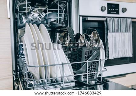 Open dishwasher with white clean dishes after washing in modern scandinavian kitchen. Clean kitchenware in open dishwashing machine.