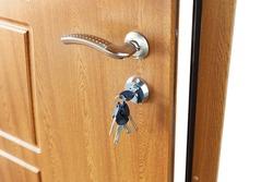 Open door handle wide angle. Door lock with keys. Brown wooden door closeup isolated. Modern interior design, door handle. New house concept. Real estate.